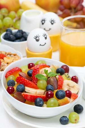 fresh fruit salad, cream and painted eggs for breakfast, vertical, close-up photo