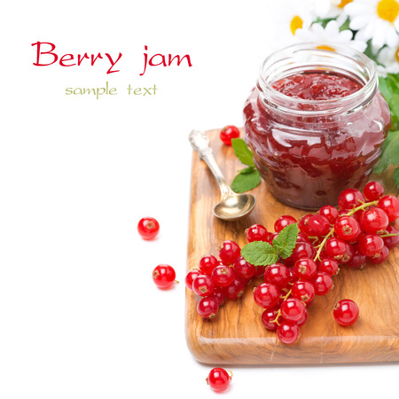 berry jam in a glass jar and fresh red currants on a wooden board, isolated on white photo