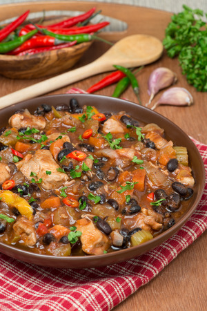 meat dish: stew with black beans, chili, chicken and vegetables, vertical Stock Photo