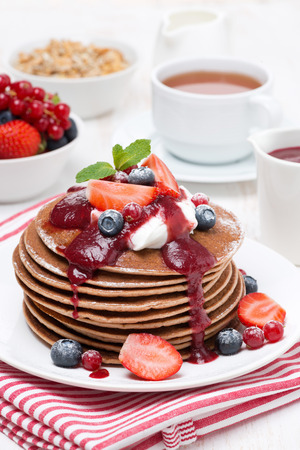 pancakes with cream, fruit sauce and berries for breakfast, vertical photo