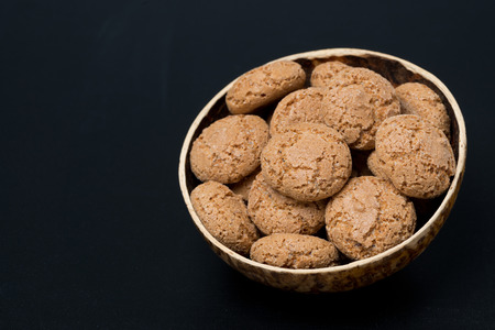 biscotti cookies in a bowl on a black background, horizontal photo