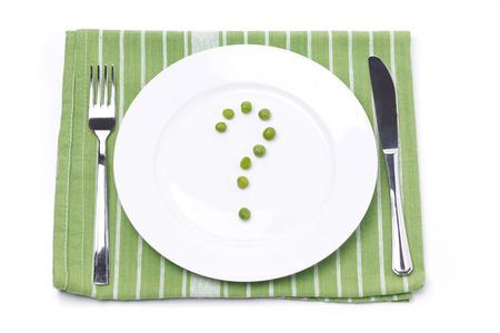punto interrogativo: piatto vuoto con piselli verdi a forma di punto interrogativo, concetto, isolato su bianco Archivio Fotografico