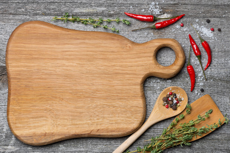 figured wooden cutting board, spoon, spatula, herbs and spices, space for recipe, top view