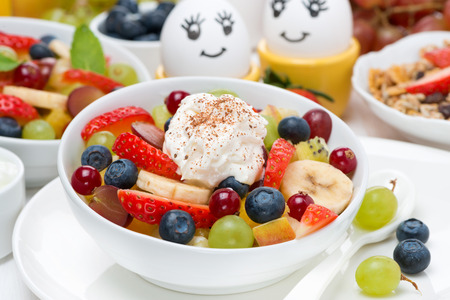 Fresh fruit salad with whipped cream and painted eggs for breakfast, close-up photo