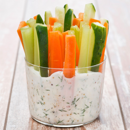 fresh vegetables in a yoghurt sauce in a glass on wooden table