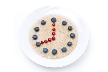 dial plate: plate of oatmeal with berries in the form of dial, isolated on white