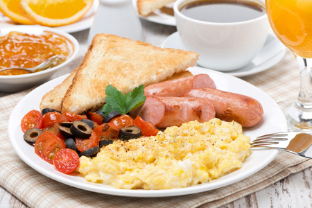 scrambled: scramble eggs with tomatoes, sausage and toast for breakfast Stock Photo