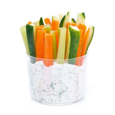 fresh vegetables in a yoghurt sauce in a glass, close-up, isolated on white Foto de archivo