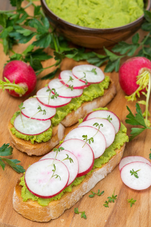 ciabatta with pate of avocado and fresh radish on wooden board photo
