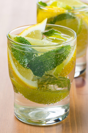 Cold fresh lemonade with lemon, lime and mint in glass photo