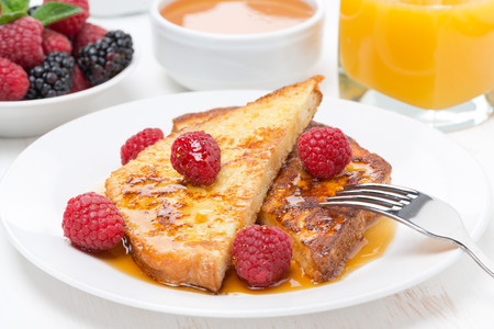 traditionally french: French toast with raspberries and honey for breakfast, close-up, horizontal Stock Photo