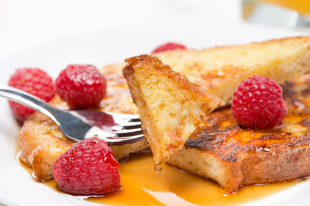 traditionally french: French toast with raspberries and maple syrup, close-up