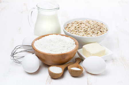 milk, cereal and ingredients for baking on white wooden table, horizontal photo