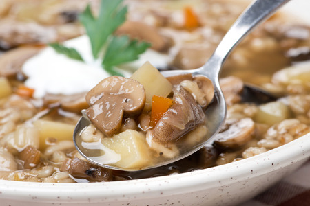 mushroom soup with pearl barley in a spoon, close-up photo