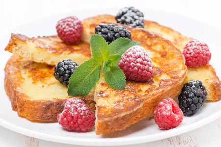 traditionally french: French toast with fresh berries, mint and powdered sugar, close-up