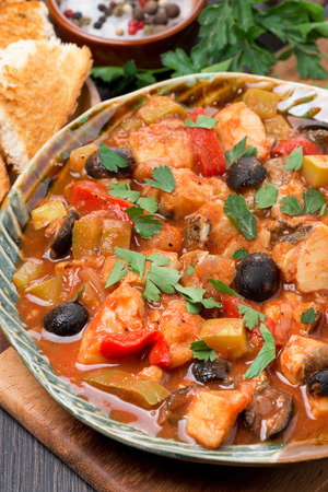 Fish stew with olives in tomato sauce on a plate, top view, vertical photo