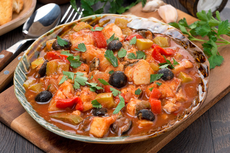 Fish stew with olives in tomato sauce on a plate, horizontal photo