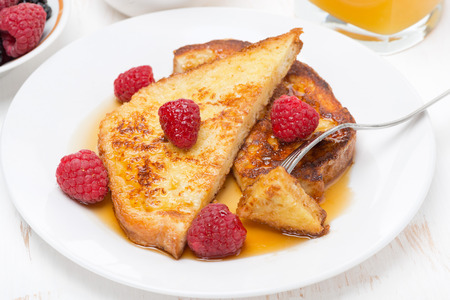 traditionally french: French toast with raspberries and maple syrup, top view, close-up