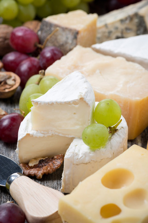 assortment of cheeses and grapes, close-up, vertical photo