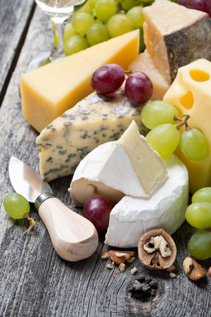 assortment of fresh cheeses, grapes and walnuts on a wooden background, close-up, vertical photo