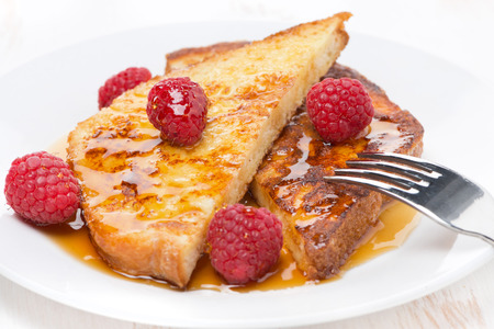 traditionally french: French toast with raspberries and honey, close-up, horizontal