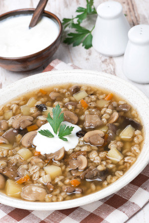 mushroom soup with vegetables and pearl barley, vertical, close-up photo