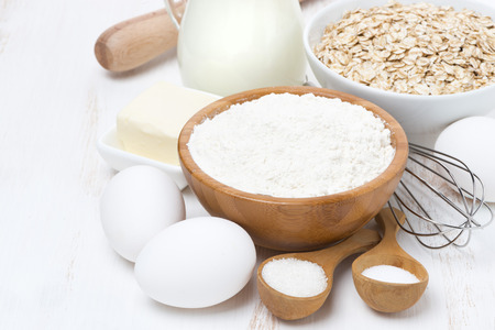 milk, cereal and ingredients for baking on wooden table, horizontal, close-up photo