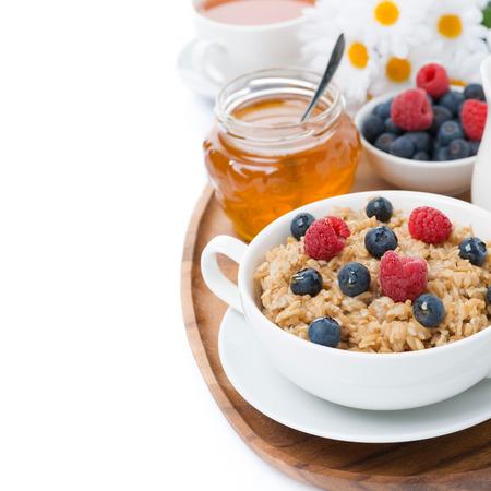 oat porridge with berries and honey, isolated on white Stockfoto