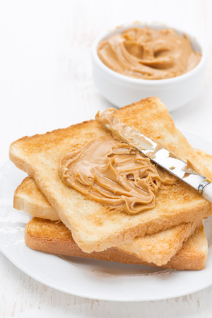toast with peanut butter, vertical, close-up