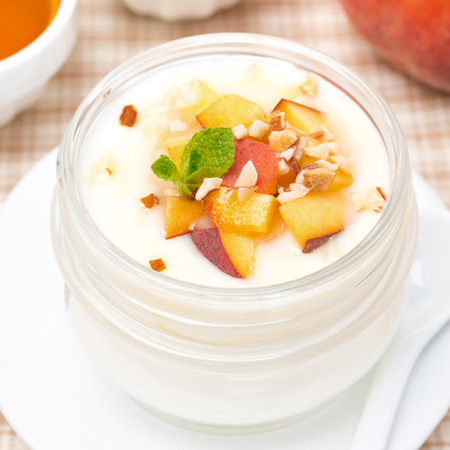 ooking: vanilla yogurt with fresh peaches and nuts, top view, close-up Stock Photo