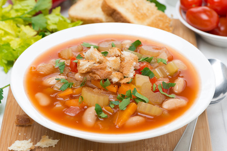 minestrone: vegetable minestrone with croutons on a plate, close-up, horizontal