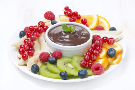 assorted fruit with chocolate sauce on a plate, horizontal photo