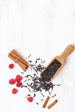 Dried tea leaves, cinnamon and raspberries on a white wooden background, top view photo