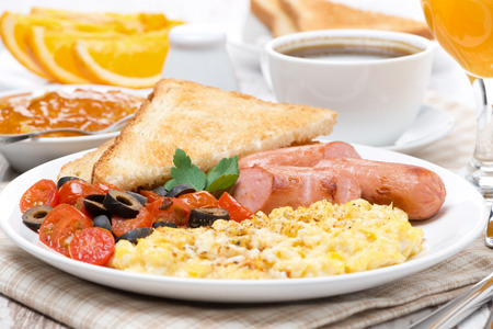 scramble eieren met tomaten, gegrilde worstjes en toast op de plaat, close-up Stockfoto