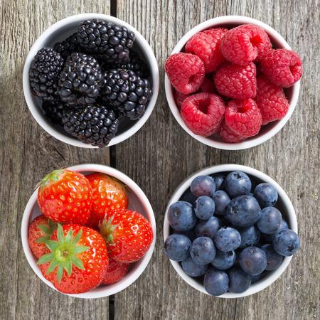 frutas: fresas, arándanos, moras y frambuesas en tazones, vista desde arriba, primer plano