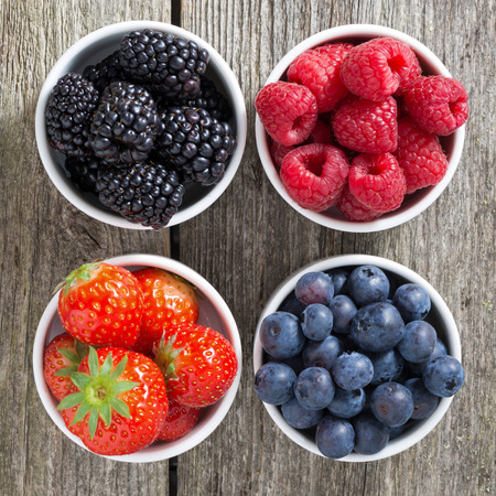 fruit mix: strawberries, blueberries, blackberries and raspberries in bowls, top view, close-up