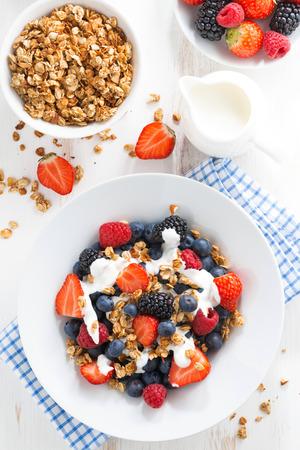 fresh berries, yogurt and muesli for breakfast, top view, vertical Foto de archivo
