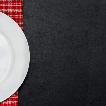 empty white plate on a checkered napkin and black background for your text