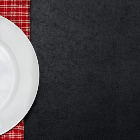 tovagliolo: piatto vuoto bianco su un tovagliolo a scacchi e sfondo nero per il testo Archivio Fotografico