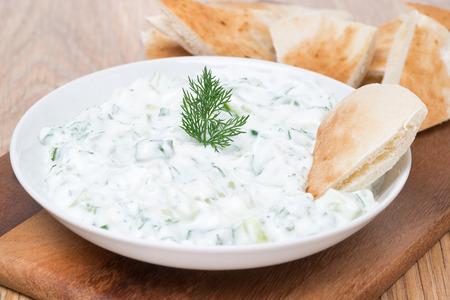 yoghurt sauce tzatziki with herbs, cucumber and garlic, close-up, horizontal