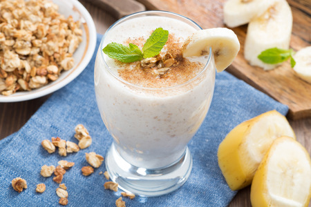 fruit shake: milkshake with banana, granola and cinnamon in a glass, top view, horizontal