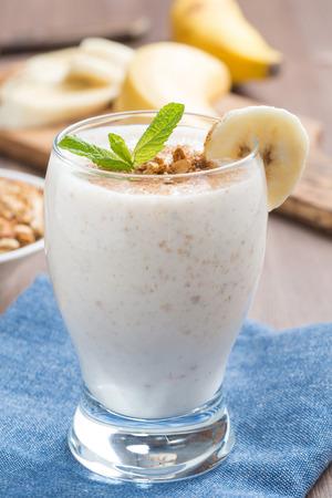 milkshake with banana, granola and cinnamon in a glass, vertical, close-up Standard-Bild