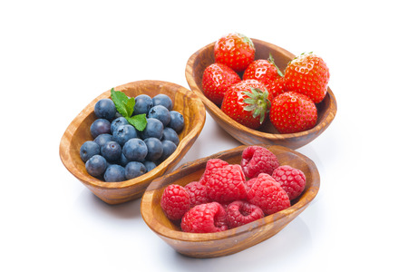 raspberries, blueberries and strawberries in a wooden bowls, isolated on white photo