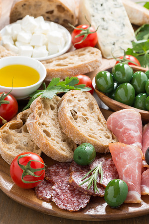 assorted Italian antipasti - deli meats, fresh cheese, olives and bread, vertical, close-up