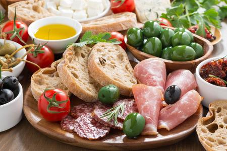 diverse Italiaanse antipasti - vleeswaren, verse kaas, olijven en brood, horizontale Stockfoto