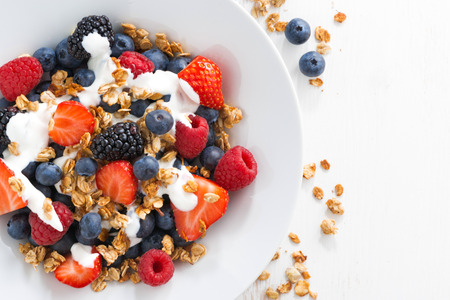 breakfast cereal: fresh berries, yogurt and homemade granola for breakfast, close-up, top view, horizontal