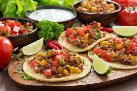 chili sauce: Mexican cuisine - tortillas with chili con carne and tomato salsa on wooden board, horizontal Stock Photo