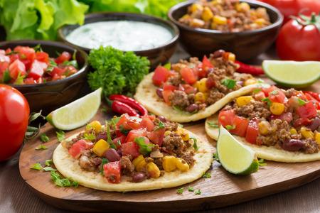Mexican cuisine - tortillas with chili con carne and tomato salsa on wooden board, horizontal Standard-Bild