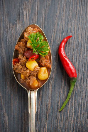 chili sauce: Mexican dish chili con carne in a spoon on a wooden background, concept photo, top view, vertical