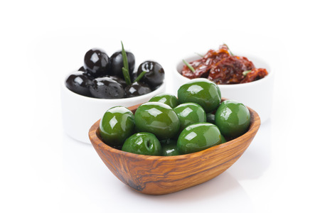 sundried: green and black olives, sun-dried tomatoes in a bowls, isolated on white Stock Photo